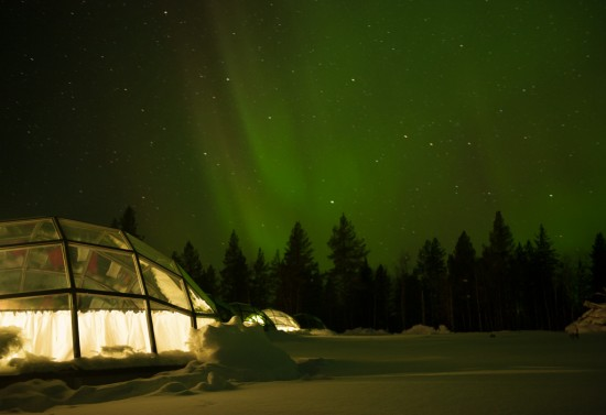 The northern lights dancing over lit (and very reflective) igloos.